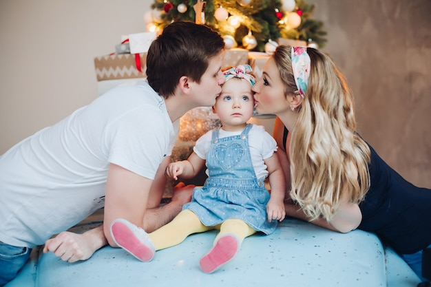 Dad and mom kissing little daughter from sides, posing in decorated for christmas room.