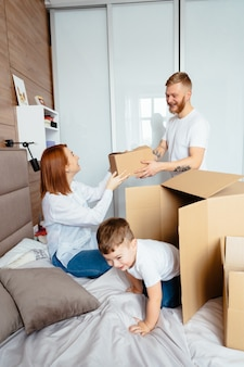 Dad, mom and little son play in the bedroom with paper boxes