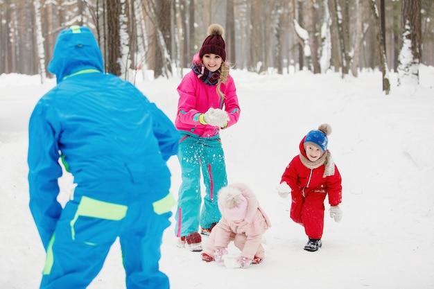 冬の服を着たお父さん、お母さん、息子と娘は、雪玉を遊んで楽しんでいます