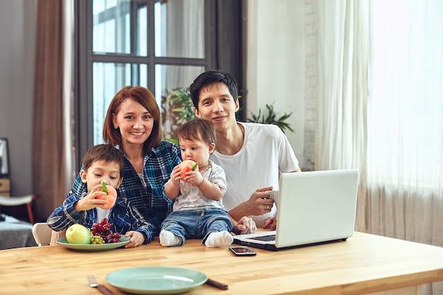 Папа, мама, сын и маленькая дочь позирует дома