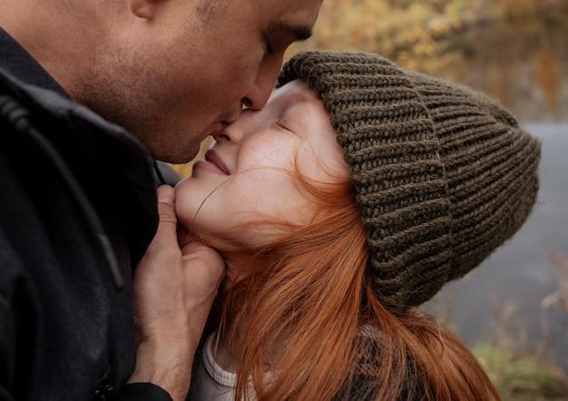 散歩中のお父さんは鼻で彼の赤い娘にキスします。