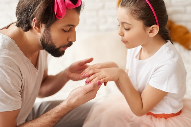 Dad paints little daughters nails with a polish.