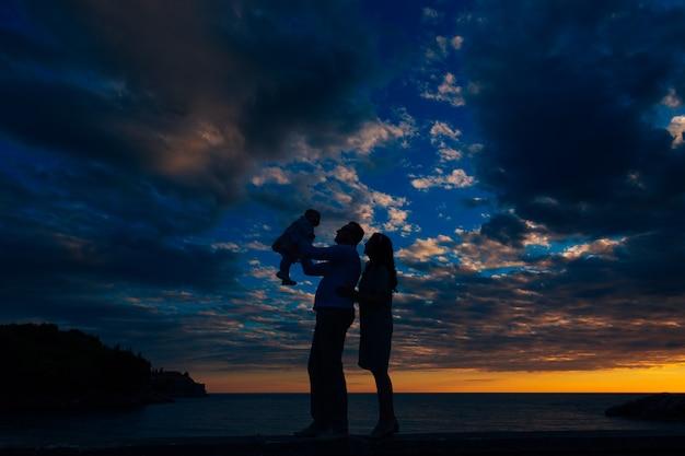 아빠는 어린 소녀를 팔에 안고 엄마가 빌라 마일로서 근처 해변에서 뒤에서 아빠를 껴안습니다.