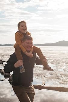 お父さんは川岸で息子と遊んでいます。美しい父と息子は晴れた日に遊んで笑って楽しんでいます。子供は父親の腕の中にいます。野外レクリエーション。
