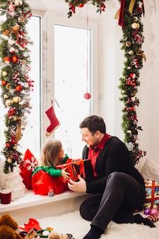 Папа играет с маленькой дочкой, перед ярким окном, украшенным на рождество