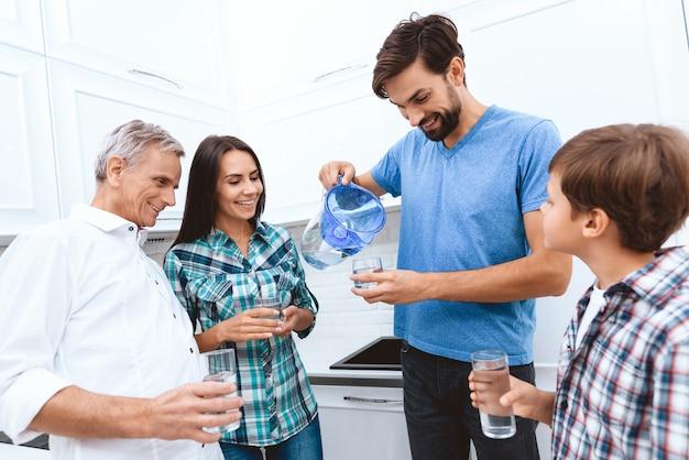 Папа наливает всю семью водой из фильтра.