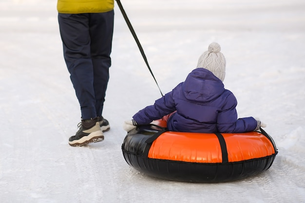 Папа тянет маленькую девочку на надувном кольце. зима, веселье, подвижные игры на коньках. спортивная ходьба. крупным планом вид сзади. зимний снежный фон. фото высокого качества