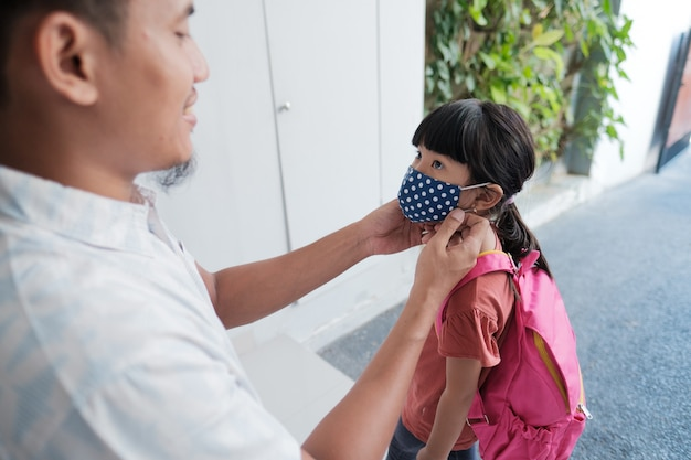 お父さんは学校に行く前にコロナウイルスから保護するために娘にマスクをかけました