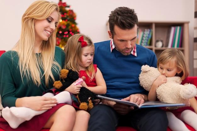 Папа читает книгу для дочерей на рождество