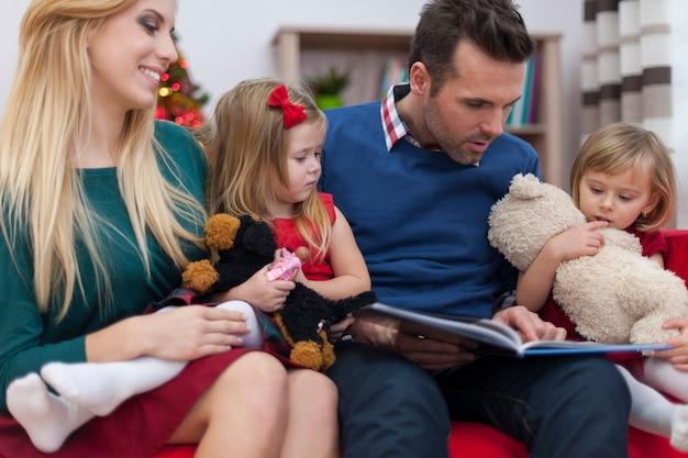 Папа читает книгу для своих маленьких дочерей на рождество