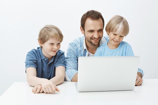 Papà che ricorda i ricordi felici delle vacanze estive con i figli. ritratto di famiglia spensierata soddisfatta di ragazzi e padre seduto al tavolo vicino al computer portatile