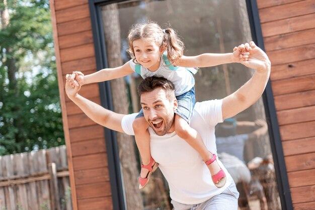 아빠는 달리고, 어깨에 앉아 있는 딸과 놀고, 아빠는 소녀의 손을 잡고, 그들은 함께 여름 산책을 하는 동안 재미있습니다.