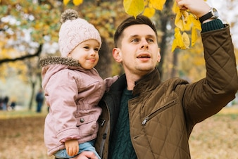 Dad showing autumn leaves his little daughter in park