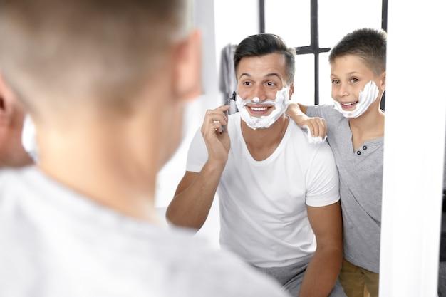 아빠는 아들에게 화장실에서 거울 근처에서 면도하는 방법을 보여줍니다.