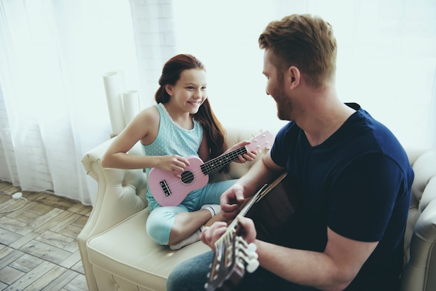 Dad shows daughter how to play guitar.