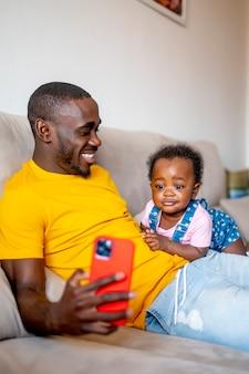 9 개월 된 딸에게 스마트 폰을 보여주는 아빠