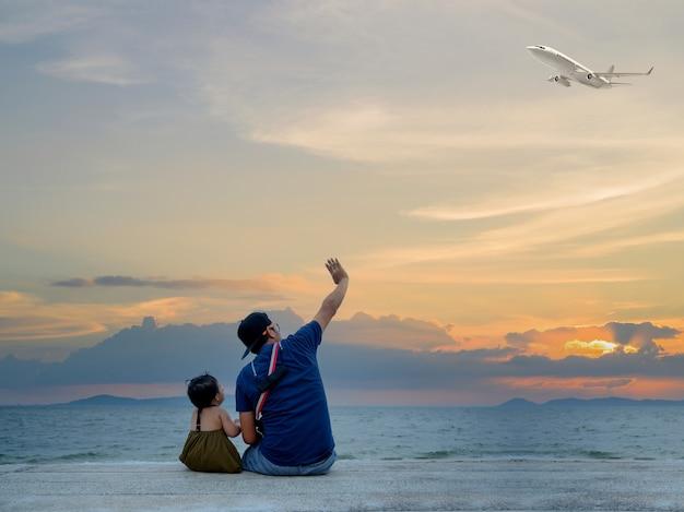 ビーチで子供と一緒に座っているお父さん。アジアの家族のライフスタイル。旅行と夏休みのリラックス