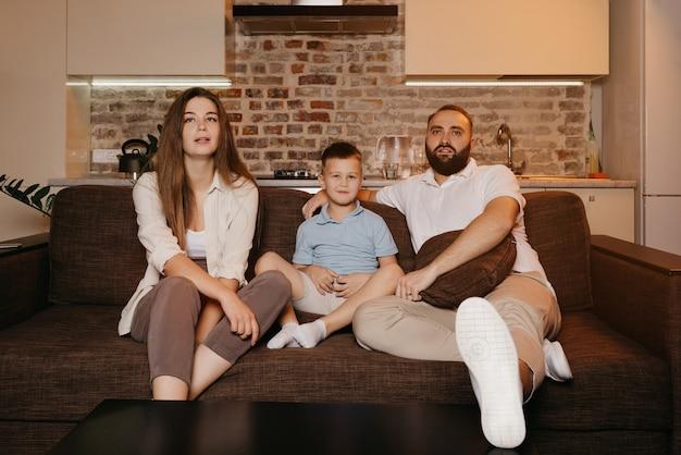 Папа, сын и молодая мама с длинными волосами с интересом смотрят телевизор на диване в квартире.