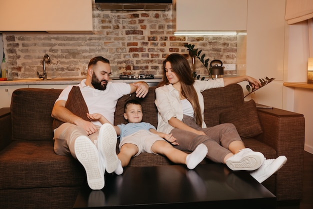 お父さん、息子、お母さんがアパートのソファで退屈なテレビ番組を見ています