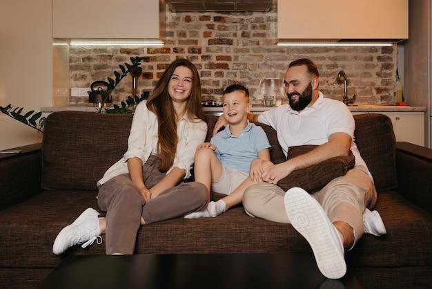 Папа, сын и мама смотрят телевизор и смеются на диване в квартире.