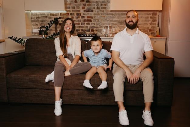 Папа, сын и мама смотрят телевизор на диване в квартире