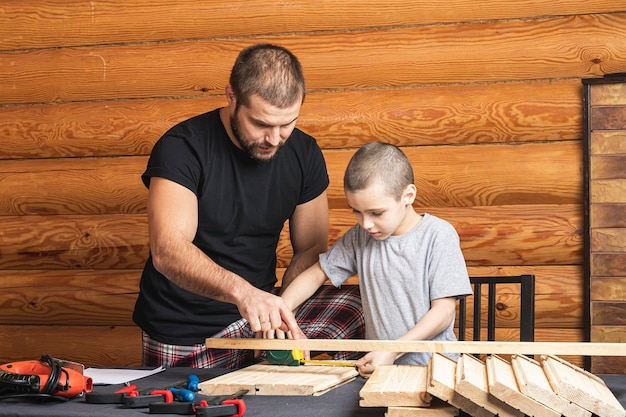 Dad and son are measure with tape wooden blocks , planning how to build a bird house