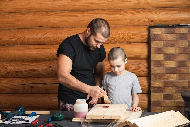 Dad and son are   painting a wooden board with a brush in red