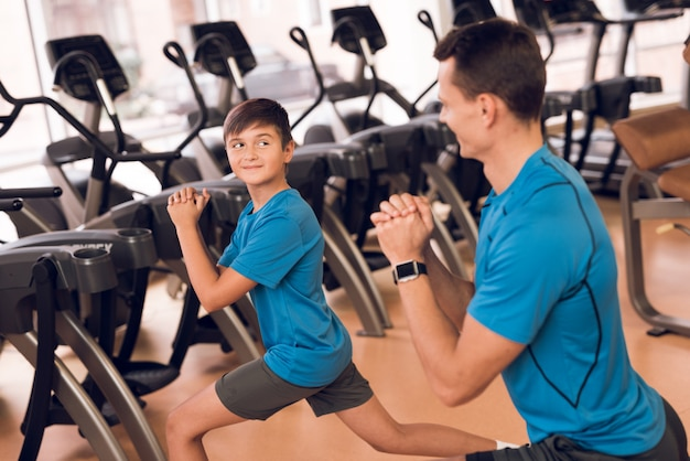 Dad and son athletes do lunges in the gym