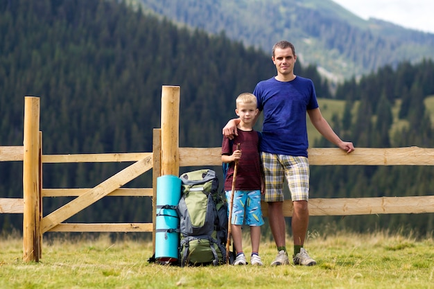 Dad and son child standing near tourist backpack at low wooden fence on green mountains covered with pine forest. active lifestyle, tourism, family relations and weekend activity concept.