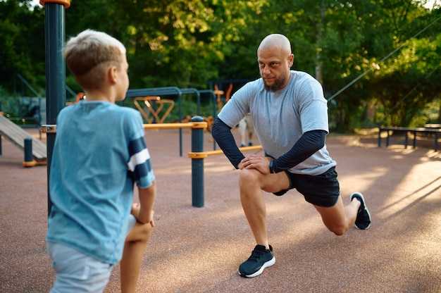 Dad and son doing exercise, sport training on playground outdoors. the family leads a healthy lifestyle, fitness workout in summer park