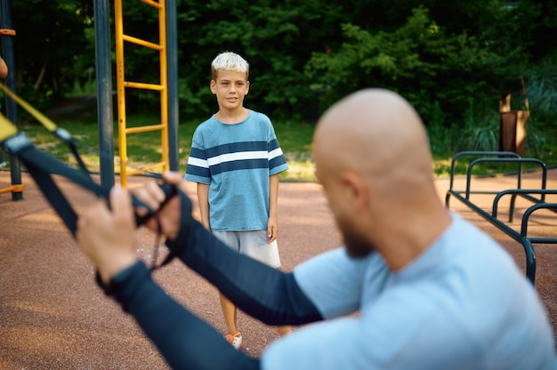 Dad and son doing exercise with ropes, playground