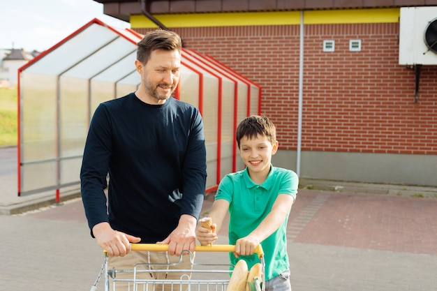 Dad and son have fun chatting out of the supermarket with shopping bags, summer day, teenagers relationship concept
