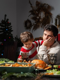 Dad and son have a fun at the table in christmas dinner