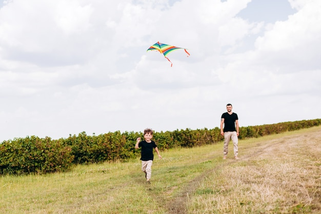 Dad and son having a funny time,launch a kite on nature