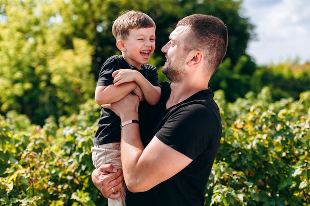 Dad and son having a funny time outdoor, hugging and laughing