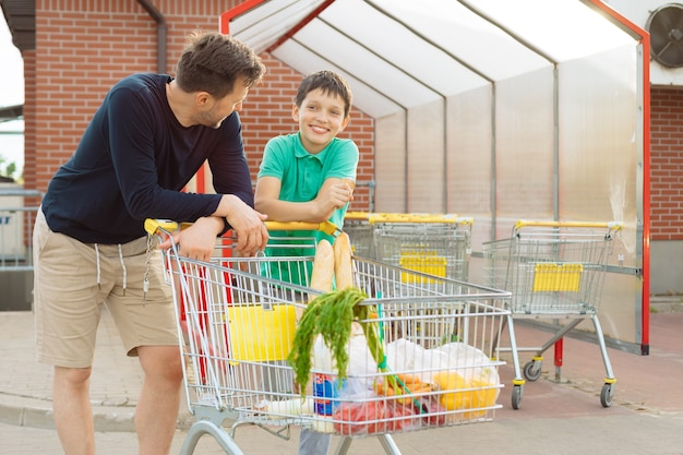 Dad and son made purchases together and walk to the car with shopping cart, spend time together, men's conversations