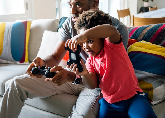 Dad and son playing game at living room together