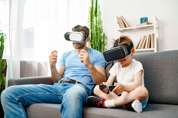 Dad and son sitting on sofa and playing games with vr glasses together