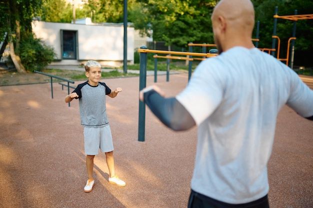 Dad and son, sport training on playground outdoors. the family leads a healthy lifestyle, fitness workout in summer park
