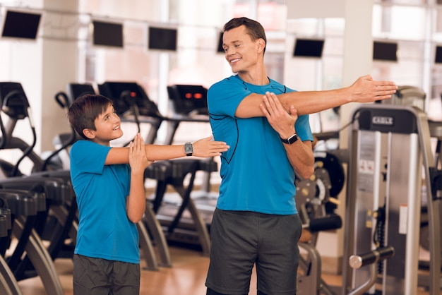 Dad and son do stretching in the gym.