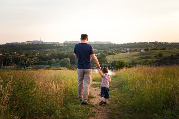 Dad and son walk in a yellow summer field in the evening