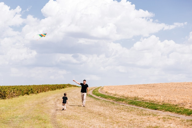 Dad and son walking outdoor,launch a kite on naturee