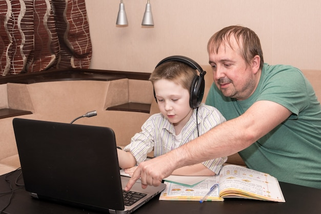 Dad and son watches an e-learning video in the living room of the house.