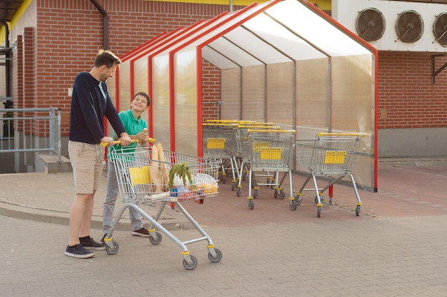 Dad and son went shopping together and walk to the car with shopping cart, spend time together