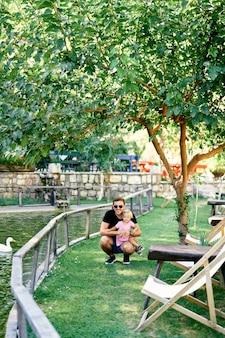 아빠는 녹색 잔디에 오리가 있는 연못 근처에서 어린 소녀와 쪼그리고 앉았다