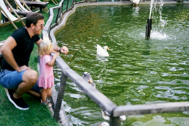아빠는 오리가 있는 연못 근처에서 어린 소녀와 쪼그리고 앉았다