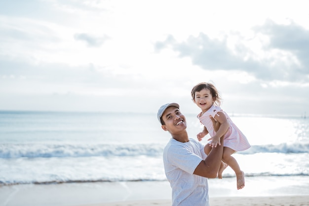 Dad swinging his toddler girl into the air on the beach having fun together