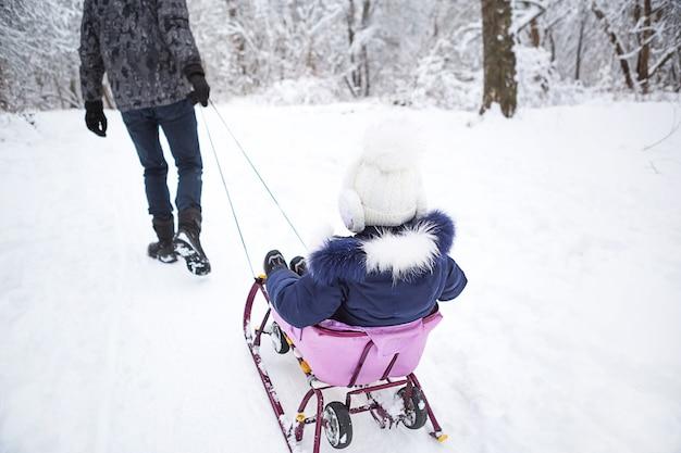 お父さんは幼い娘を冬の雪の森の中を上り坂のそりに乗せます。アクティブな家族の野外活動