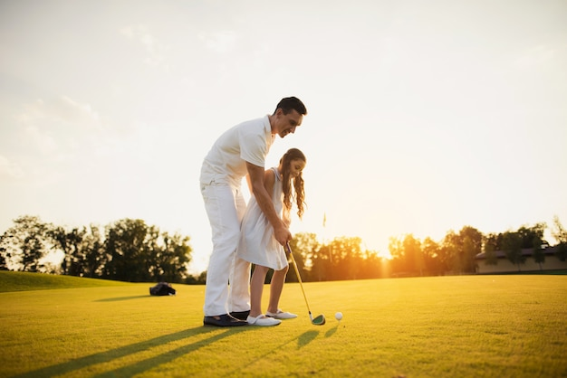 Dad teaches child to take golf shot family hobby.
