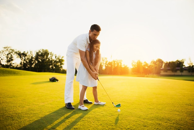 Dad teaches child take shot golfing family hobby.
